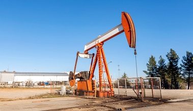 Close up view of the pump jack. A pumpjack is the overground drive for a reciprocating piston pump in an oil well. Modern pumpjacks are powered by a prime mover.